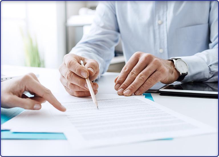 Mężczyzna ołówkiem wskazuje dokument
